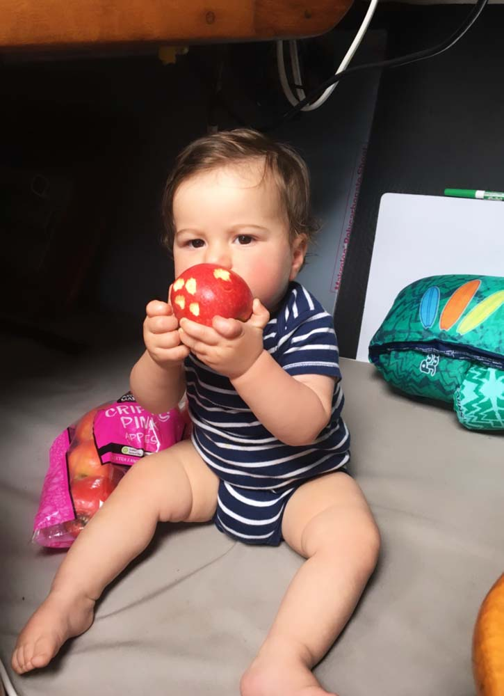Boat baby munching on an apple in the quarterberth